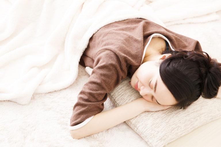 ラグに枕をひいて寝ころぶ女性