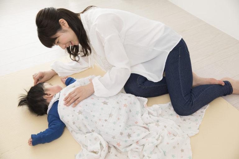 床暖房対応のラグで子供を寝かしつけている女性